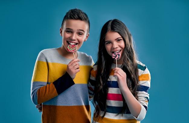 Un ragazzo e una ragazza alla moda in maglioni multicolori mangiano lecca-lecca caramelle isolati su un blu.