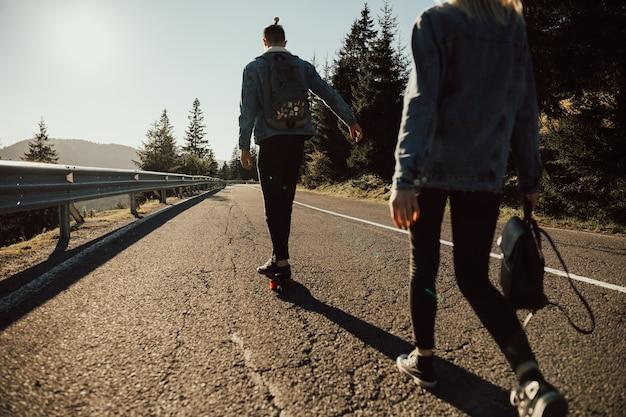 Ragazzo alla moda cavalca uno skateboard sulla strada in montagna