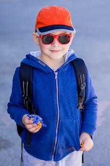Ragazzo alla moda in occhiali da sole con il giocattolo in mano