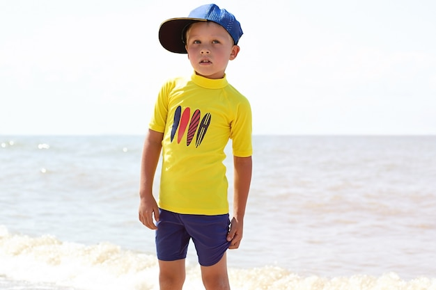 Ragazzo alla moda in costume da bagno sulla costa del mare.