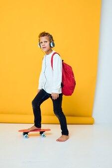 Ragazzo alla moda con uno zaino rosso che indossa le cuffie da skateboard sfondo isolato