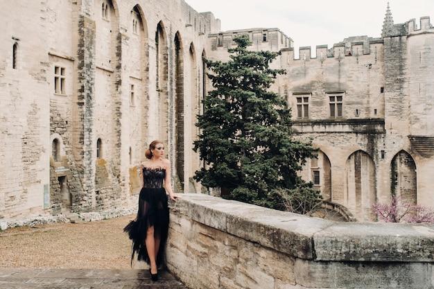Una sposa elegante in un abito da sposa nero posa nell'antica città francese di avignone. modello in un bellissimo vestito nero. servizio fotografico in provenza.