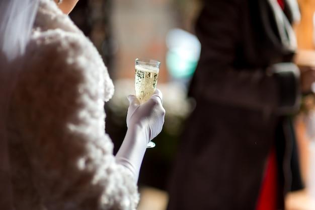 La sposa alla moda tiene il vetro con champagne nelle mani