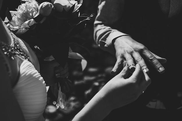 Elegante sposa indossa anello d'oro sulla mano del dito dello sposo.