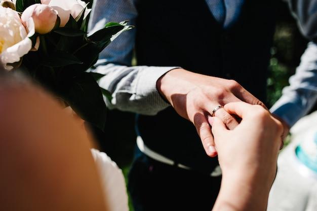Elegante sposa con un bouquet di peonie indossa un anello d'oro sul dito della mano dello sposo