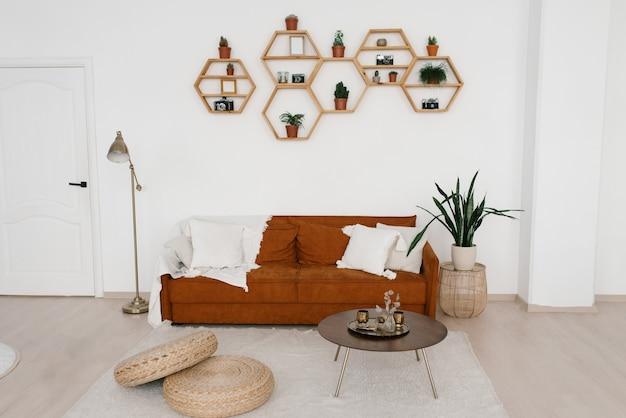Elegante divano marrone con cuscini e una coperta, lampada da terra, ripiani in vaso di fiori a nido d'ape