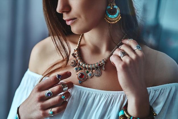 Elegante donna boho bruna che indossa una camicetta bianca con grandi orecchini, collana con pietra e anelli d'argento. vestito bohemien zingaro hippie indiano alla moda con dettagli di gioielli imitazione