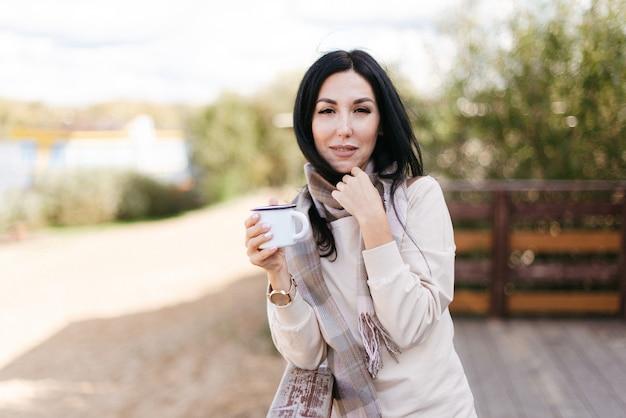 Elegante ragazza bruna in una sciarpa che tiene una tazza di ferro nelle sue mani