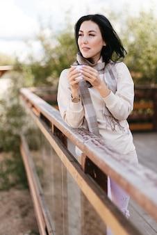 Elegante ragazza bruna in una sciarpa si trova vicino alla ringhiera e beve da una tazza di ferro