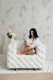 Elegante ragazza bruna con i piedi nudi e un telefono seduto su una poltrona bianca