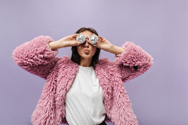 Elegante signora dai capelli castani in semplice t-shirt e maglione rosa a maniche lunghe alla moda che tiene due piccole palle da discoteca sul muro lilla