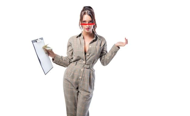 Elegante bruna sta in studio su un bianco con una tavoletta in mano