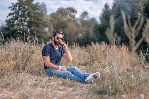 Elegante uomo brutale che fuma uno svapo sul suolo della foresta Foto Premium