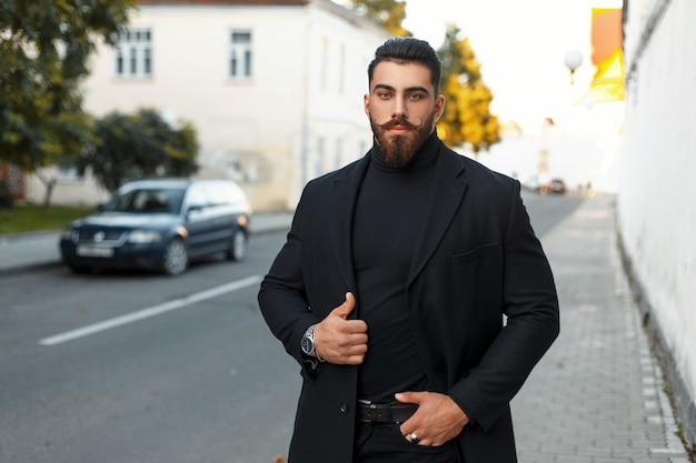 Elegante uomo brutale con la barba in un cappotto alla moda nero cammina per strada