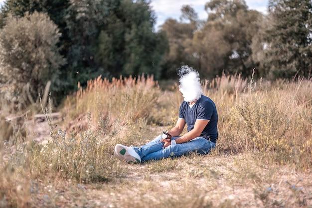 Elegante fumatore brutale che soffia molto fumo utilizzando un dispositivo elettronico per il fumo di vape in una radura della foresta