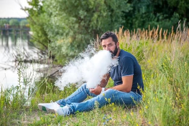 Elegante fumatore brutale che fuma una sigaretta elettronica alla luce del giorno