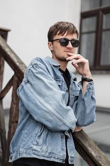 Modello di giovane uomo brutale alla moda in una giacca di jeans alla moda in occhiali da sole con la barba sta riposando vicino a una ringhiera di legno in città in una giornata di primavera.il hipster moderno ragazzo cool è gode di vacanze all'aperto
