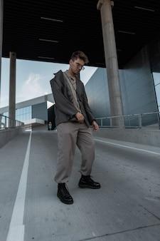 Elegante modello di uomo d'affari con occhiali da sole vintage in abito grigio alla moda con giacca, camicia, pantaloni e stivali cammina in città