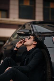 Un uomo d'affari alla moda fuma sigari vicino a un'auto di lusso. moda e affari.