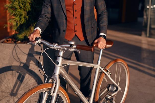Elegante uomo d'affari con la bicicletta in piedi sulla strada della città