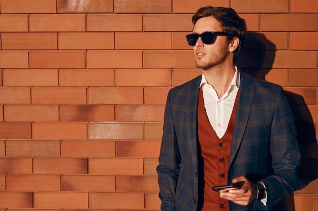 Elegante uomo d'affari con lo smartphone vicino al muro di mattoni