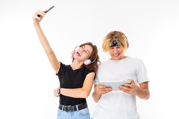 L'uomo e la donna biondi caucasici alla moda fanno il selfie e ascoltano la musica isolata sulla parete bianca