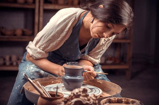 Elegante scultrice ceramista lavora con l'argilla sulla ruota di un vasaio e al tavolo con gli strumenti. prodotti fatti a mano.