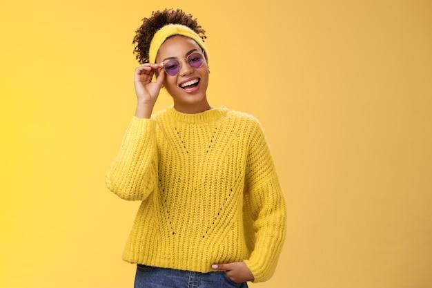 Elegante freddo fiducioso moderno millenario adolescente maglione fascia blu occhiali da sole toccando montature per occhiali sorridente ampiamente assertivo sguardo sicuro di sé sorridendo felice tenere la tasca della mano.