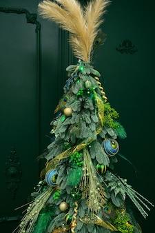Elegante albero di natale con verde chiaro, con piume di pavone in colori verde e azzurro fuoco selettivo