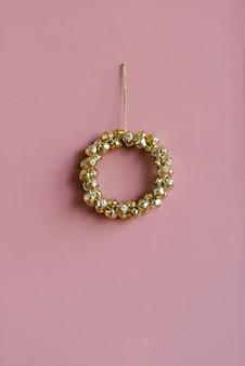 Elegante ghirlanda di natale di campane d'oro su uno sfondo rosa con spazio copyi