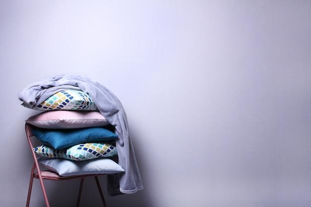 Eleganti cuscini colorati e plaid grigio nella sala sul muro grigio. cuscini blu scuro, rosa, blu sulla sedia. copi lo spazio, concetto domestico accogliente.