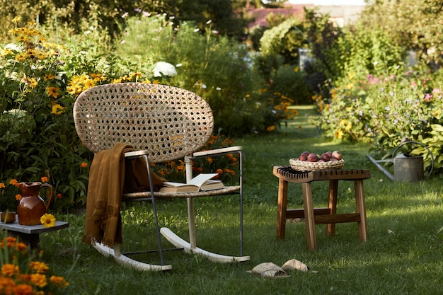 Elegante composizione di giardino di campagna con poltrona di design in rattan, panca in legno, plaid, cibo, bevande e accessori eleganti. molti fiori colorati. atmosfera estiva.