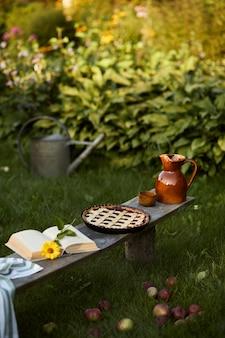 Elegante composizione di giardino di campagna con vecchia panca in legno, libro, girasole, torta, vaso in ceramica ed eleganti accessori. molti fiori colorati. atmosfera estiva.
