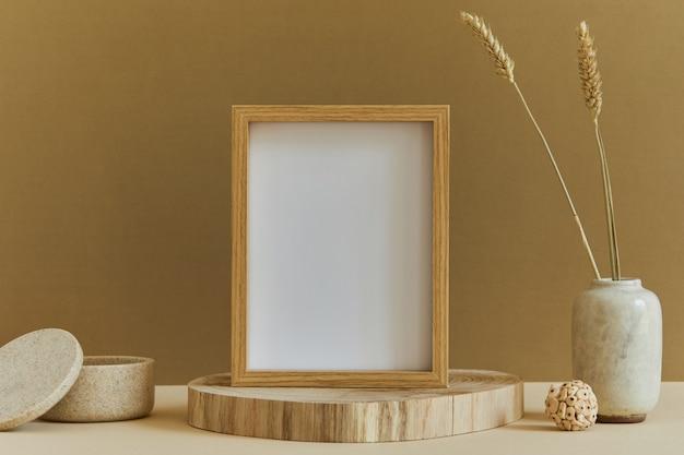 Composizione elegante di interni accoglienti e creativi con cornice per poster mock up, materiali naturali come legno e marmo, piante secche e accessori personali. colori neutri e gialli, modello.