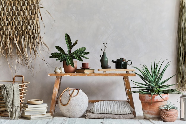 Composizione elegante di interni accoglienti del soggiorno con spazio per le copie, panca in stile retrò, vaso di argilla, stoviglie, decorazione della parete di paglia e tessuti. ispirazione rustica. vibrazioni estive. muro beige. modello.