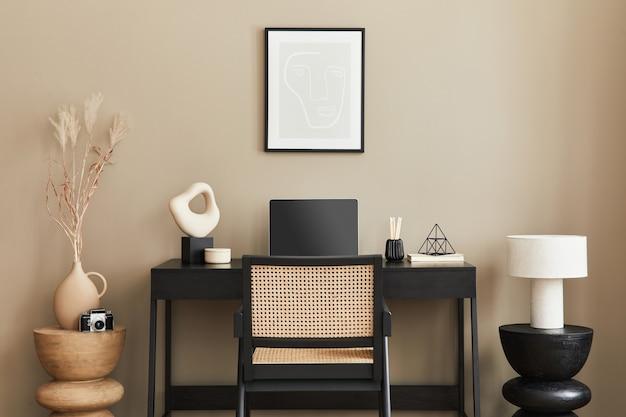 Elegante composizione di interni per l'home office con scrivania in legno nero, sedia, fiori secchi in vaso, laptop, cornice per poster mock up, tazza di caffè, orologio ed eleganti accessori per ufficio. modello.