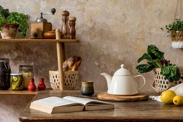 Composizione elegante dell'interno della cucina con tavolo familiare, verdure, teiera, dessert, forniture alimentari, piante e accessori da cucina nel concetto wabi sabi di arredamento per la casa
