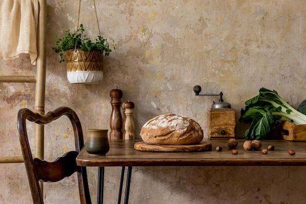 Elegante composizione degli interni della cucina con tavolo familiare, verdure, teiera, dessert, forniture di cibo, piante e accessori da cucina nel concetto di wabi sabi di arredamento per la casa.