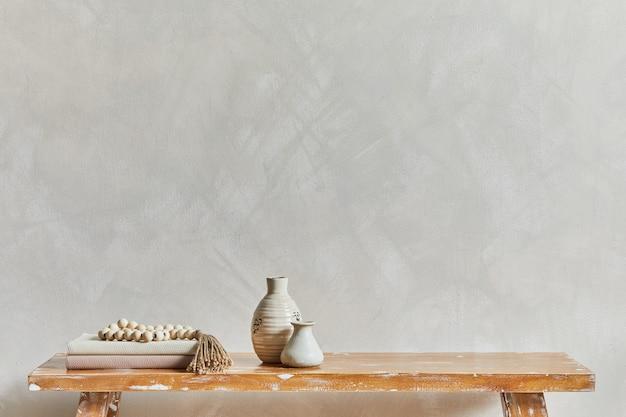 Elegante composizione dell'interno del soggiorno con copia spazio, panca in stile retrò, vasi di argilla e stoviglie. ispirazione rustica. vibrazioni estive. muro beige. modello.