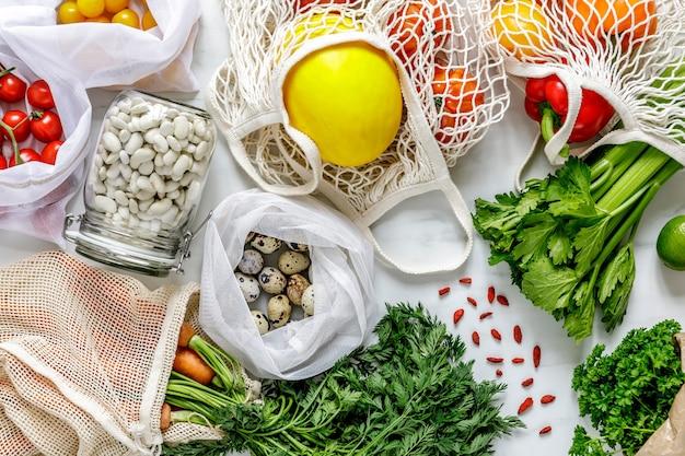 Composizione elegante sul tavolo in marmo con sacchetti zero rifiuti, noci, semi, uova, verdure biologiche e frutta ecologica. prendersi cura della terra. stop alla plastica.