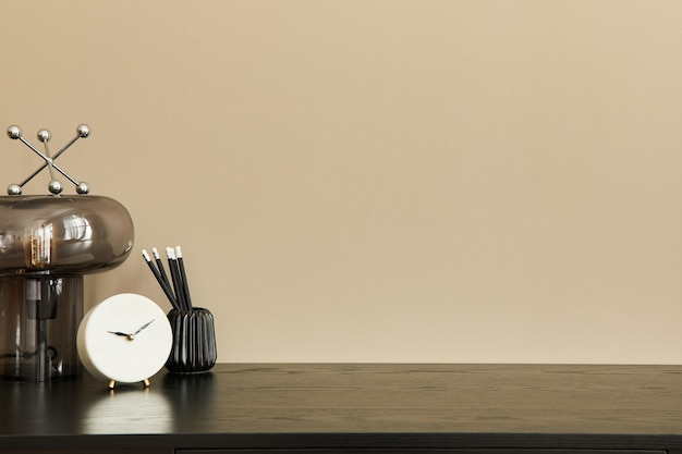 Elegante composizione di interni per ufficio con scrivania nera, lampada da tavolo di design, orologio bianco e organizer da scrivania. muro beige. copia spazio.