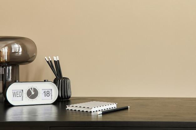 Elegante composizione di interni per ufficio con scrivania nera, lampada da tavolo di design, orologio bianco, taccuino e organizer da scrivania... parete beige. copia spazio.
