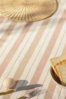 Composizione elegante dello spazio cucina all'aperto con tavolo in legno, cibo, bevande, accessori da cucina, tovaglia beige e ombre estive di alberi. atmosfera di campagna. modello.