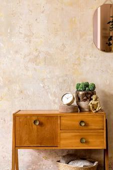 Elegante composizione di interni soggiorno retrò con comò vintage in legno, specchio rosa oro, pianta, cesto in rattan, plaid, decorazione ed eleganti accessori personali in wabi sabi home decor.