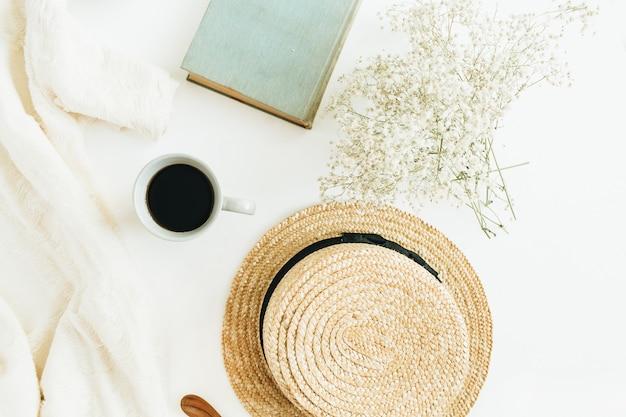Elegante composizione con caffè, libro, cappello di paglia, fiori e coperta su superficie bianca