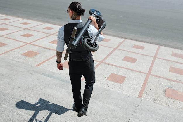 Elegante giovane fiducioso che trasporta scooter, vista dal retro
