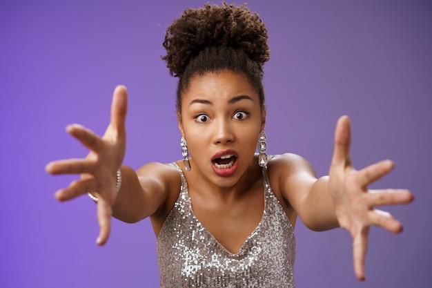 Elegante donna africana confusa in abito lucido argento che si rannicchia preoccupata estende le braccia in avanti preoccupata in piedi perplessa in preda al panico che cade durante il night club, in piedi sfondo blu. copia spazio