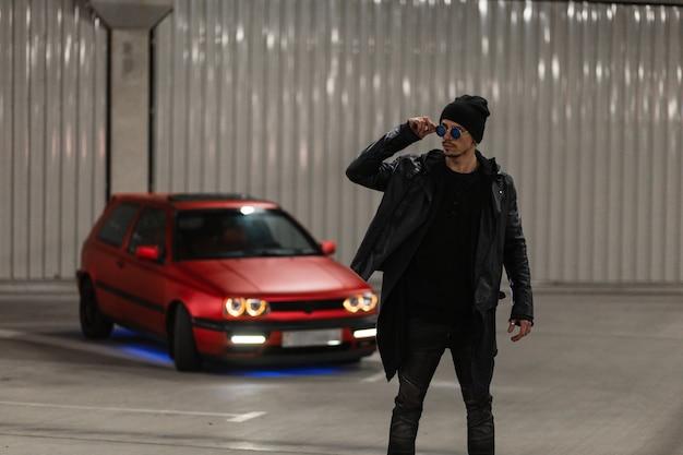 Elegante modello hipster cool in abiti alla moda: felpa con cappuccio nera, giacca di pelle, jeans e cappello con occhiali da sole vicino a un'auto rossa nella città notturna