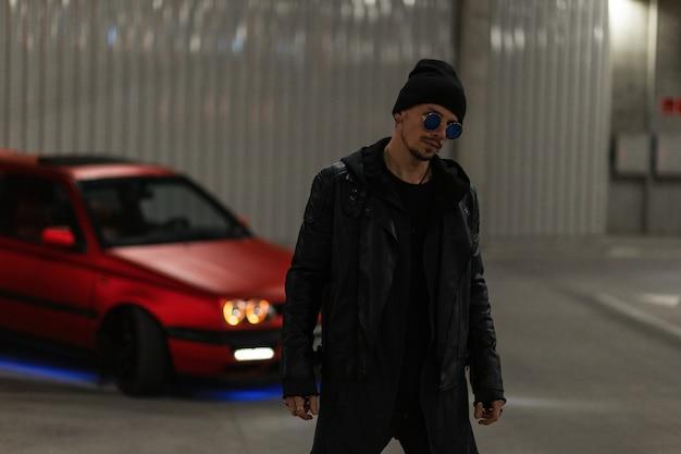 Elegante uomo alla moda con occhiali da sole e cappello in giacca di pelle alla moda e felpa con cappuccio vicino a un'auto rossa per strada di notte