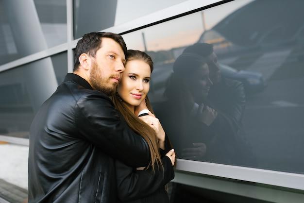Elegante coppia innamorata in abiti d'affari si abbracciano con passione e tenerezza vicino alla parete di vetro